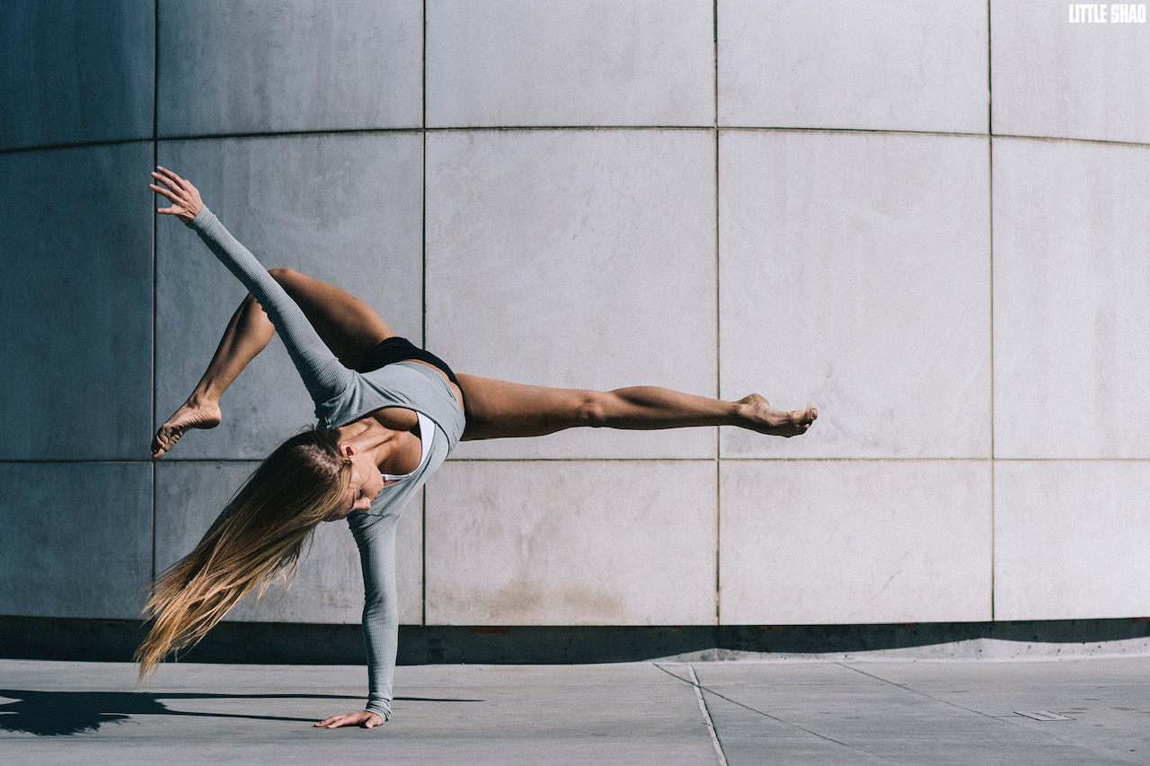 Dancer and KU alumna Kristi Griffith poses in front of a concrete wall. She is balanced on one arm with her leg horizontal to the floor and her other leg behind her.